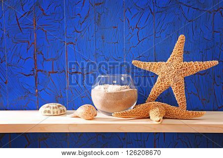 Starfishes with shells and sand on blue wooden background