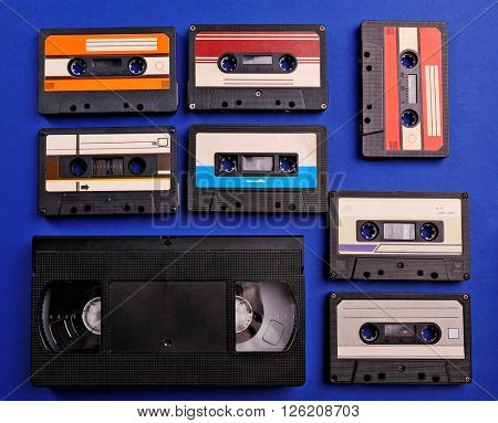 Set of old audio and video cassettes on blue background
