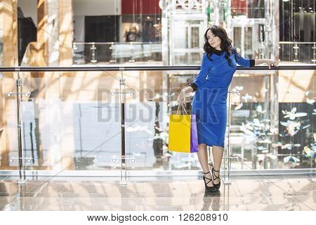 Beautiful young brunette in a blue dress with a yellow package in his hand in the shopping center of the store