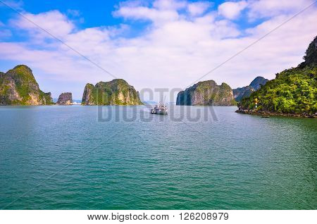 Tourist boat in Halong Bay sailing among the islands.