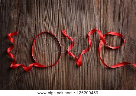 Love word with red ribbon on wooden background