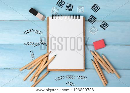 Office set with notebook, colored pencils and clips on blue background