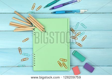 Office set with notebook, colored pencils and pens on blue background