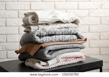 Stack of woolen clothes on black table over white brick wall background