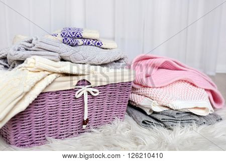 Piles of woolen clothes with basket on white carpet in light interior