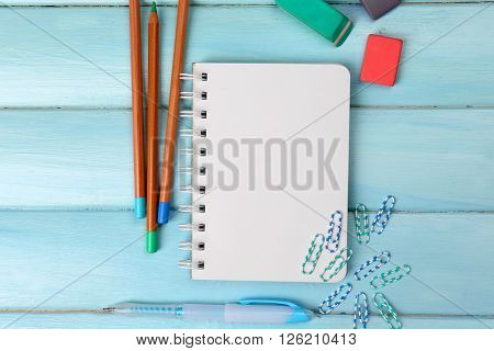Office set with notebook, colored pencils and erasers on blue background