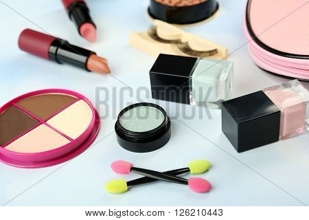 Makeup set with beautician, false eyelashes and cosmetics on blue blurred background
