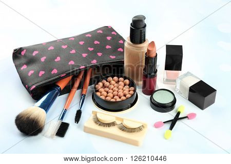 Makeup set with beautician, false eyelashes, brushes and cosmetics on blue background