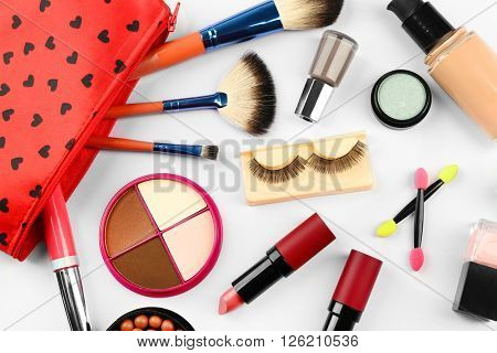 Makeup set with beautician, false eyelashes, brushes and cosmetics on white background