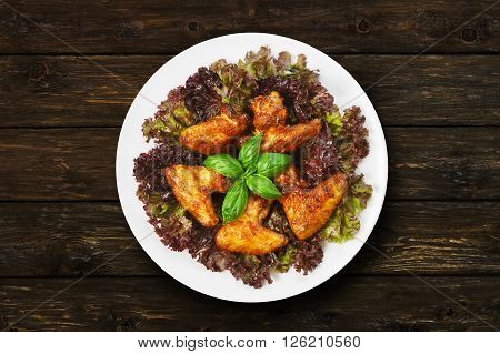 American cuisine, restaurant food -  fried roasted chicken wings on lettuce with basil at round white plate at wooden rustic background. Top view, flat lay