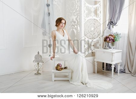 Wedding dress fashion. Beautiful young bride in vintage wedding dress indoors. White wedding dress at model. Girl shows wedding fashion in decorated interior with flowers, high key.