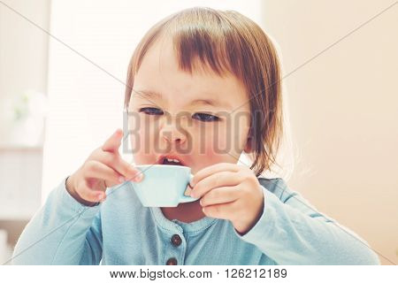 Happy Toddler Girl Drinking From A Teacup