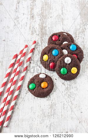chocolate cookies with sugar coated candy on a white wooden background
