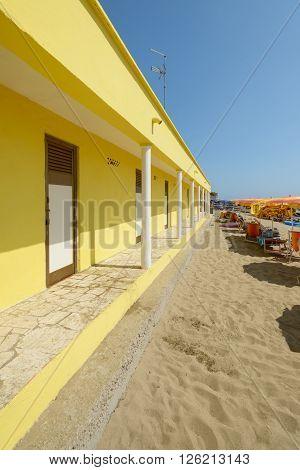 typical italian beach with yellow locker room