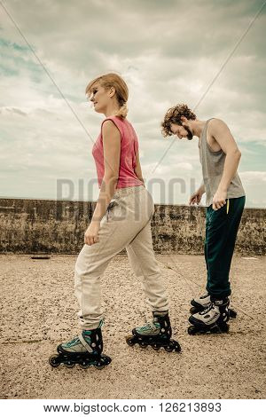 Friendship and spending time together. Outdoors activities sport and free time. Summertime exercising.. Young couple have fun together rollerblading in park learning.