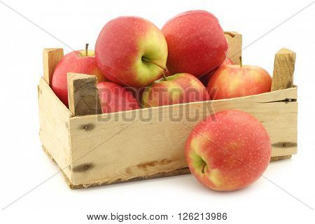 fresh red and yellow apples in a wooden crate on a white background