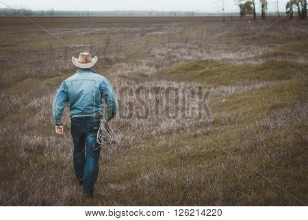 Cowboy is on the grass withered in the steppe the view from the back