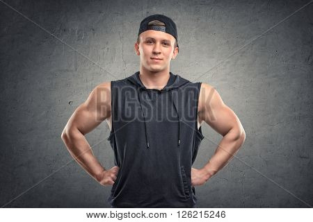 Waist-up portrait of smiling handsome muscled young man with his hands on hips looking directly at the camera