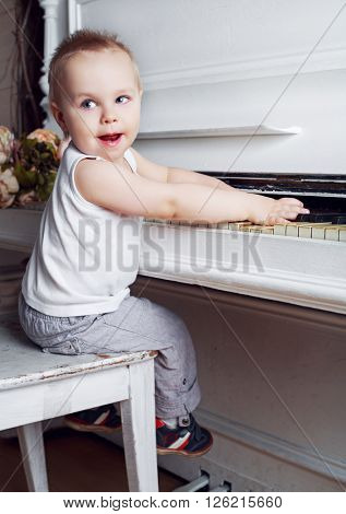 one year old baby boy playing an old piano