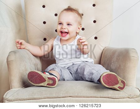 happy one and a half year old boy sitting in the chair at home