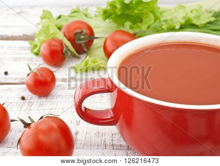 Tomato Soup In Red Ceramic Bowl On Rustic Wooden Background. Healthy Food Concept. Soft View