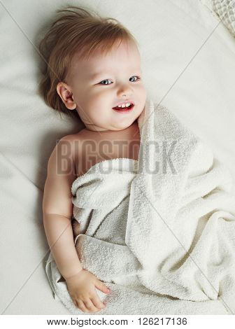 one year old baby in bed with towels after taking a bath