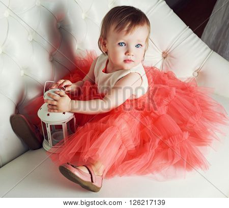 adorable baby wearing a dress on the sofa at home