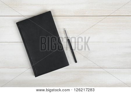 Flat lay of black notebook and black pen on light wooden surface. Composition.
