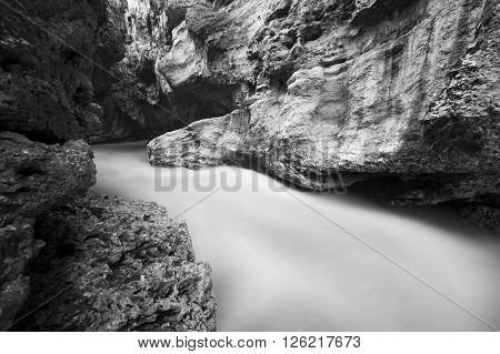 The mountain river in the gorge. Water on the long exposure. Landscape of the river between the rocks. Black and white.