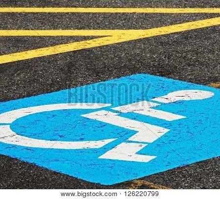 Disabled parking logo tipping over beneath yellow lines.