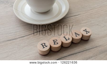 Relax Text On Wooden Table With Coffee Cup, Closeup Shot