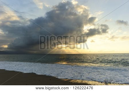 Ocean sunset sun rays is a bright burst of sunrays breaking through a massive cloud over hanging a beutiful golden blue seascape.