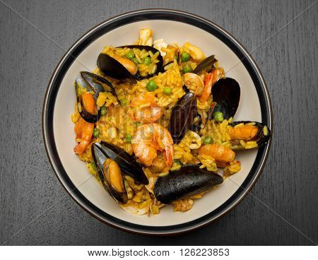 a dish with paella and seafood on wood