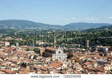 Florence Italy cityscape showing the surrounding hills and the ornate marble facade of Santa Croce Church. Copy space in sky if needed.