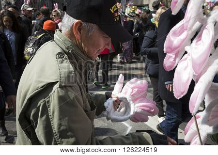 NEW YORK - MAR 27 2016: A street vendor holds several pairs of pink and white bunny ears to sell on Easter Sunday during the traditional Easter Bonnet Parade in Manhattan on March 27, 2016.