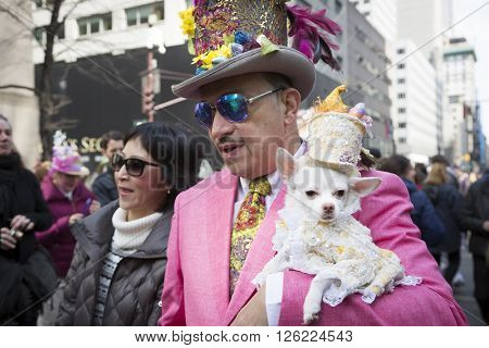 NEW YORK - MAR 27 2016: A dog wearing an Easter costume is carried by its owner on 5th Avenue Easter Sunday during the traditional Easter Bonnet Parade in Manhattan on March 27, 2016.