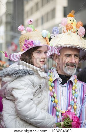 NEW YORK - MAR 27 2016: A young girl wearing a decorative Easter bonnet is carried by her father Easter Sunday on 5th Avenue at the traditional Easter Bonnet Parade in Manhattan on March 27, 2016.