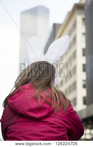 NEW YORK - MAR 27 2016: A young girl wearing decorative Easter Bunny ears Easter Sunday on 5th Avenue takes part in the traditional Easter Bonnet Parade in Manhattan on March 27, 2016.