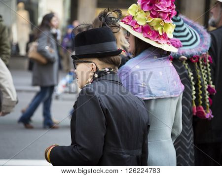 NEW YORK - MAR 27 2016: Three women wearing a decorative Easter bonnets walk along 5th Avenue on Easter Sunday for the traditional Easter Bonnet Parade in Manhattan on March 27, 2016.