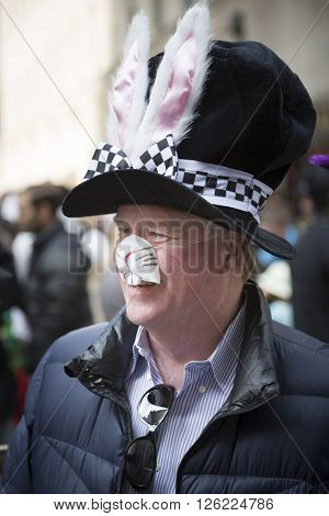 NEW YORK - MAR 27 2016: A man wearing a black hat with bunny ears walks along 5th Avenue on Easter Sunday for the traditional Easter Bonnet Parade in Manhattan on March 27, 2016.