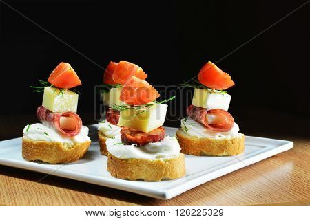 Fingerfood, cheese, salami, sausage slices and tomatoes on white platter over dark background.