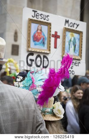 NEW YORK - MAR 27 2016: A man holding a religious sign stands on 5th Avenue in front of St Patricks Cathedral Easter Sunday during the traditional Easter Bonnet Parade in Manhattan on March 27, 2016.