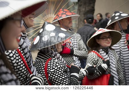 NEW YORK - MAR 27 2016: A group of people in red, white and black Asian inspired outfits and conical hats Easter Sunday at the traditional Easter Bonnet Parade on 5th Ave in Manhattan, March 27, 2016.