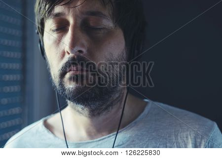 Unshaven adult man listening to music on headphones enjoy favorite song with his eyes closed.