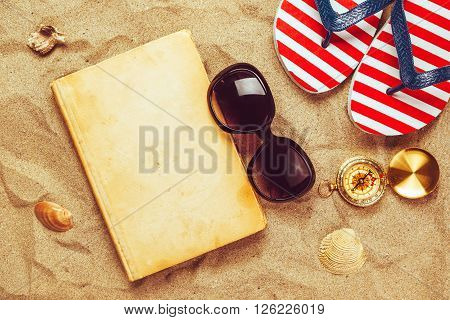 Beach ready summer holiday vacation accessories on sandy beach summertime lifestyle objects in flat lay top view arrangement.