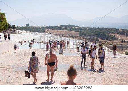 PAMUKKALE TURKEY - September 13 2015: Tourists regard the travertines with pools and terraces at Pamukkale. Pamukkale is included in the UNESCO World Heritage List.