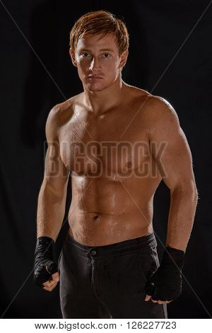 Side view of muscular man boxing on black background.