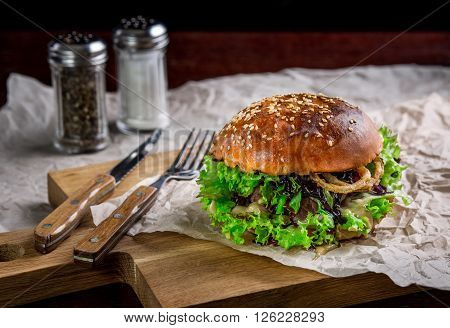 Sandwich with ostrich burger, onion, sauce and lettuce. Burger is on the table with paper and salt and pepper shakers