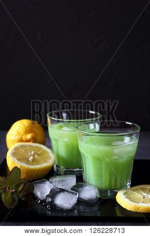 Cactus juice lemons and ice on dark background
