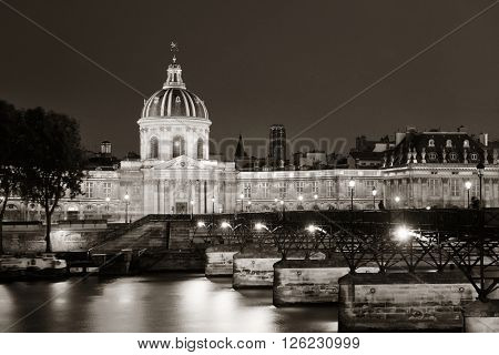 River Seine with Pont des Arts and Institut de France at night in Paris, France.